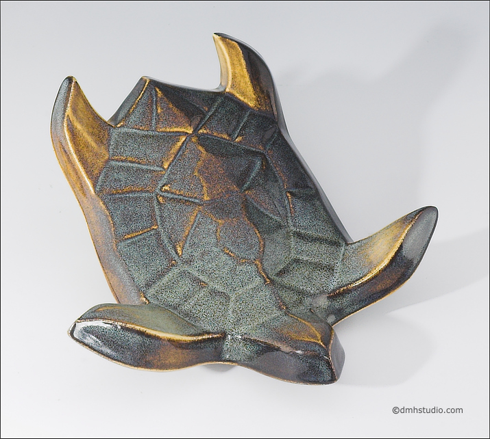 Large image of Flying Sea Turtle sculpture in gold and green glaze, seen  from above, facing down and to the viewers right.