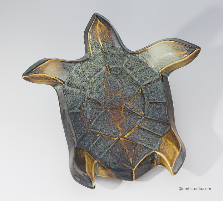 Large image of Flying Sea Turtle sculpture in gold and green glaze, seen  from above, facing top of the page.