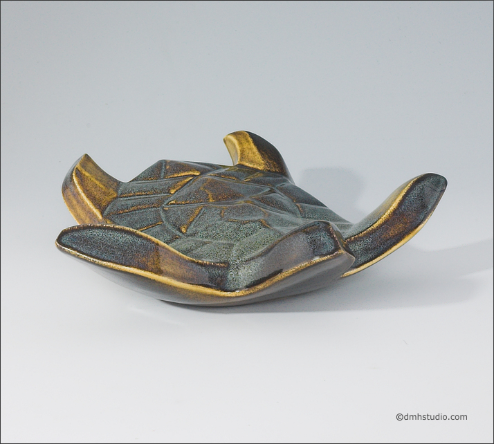Large image of Flying Sea Turtle sculpture in gold and green glaze, seen slightly from above, landed toward the viewer.